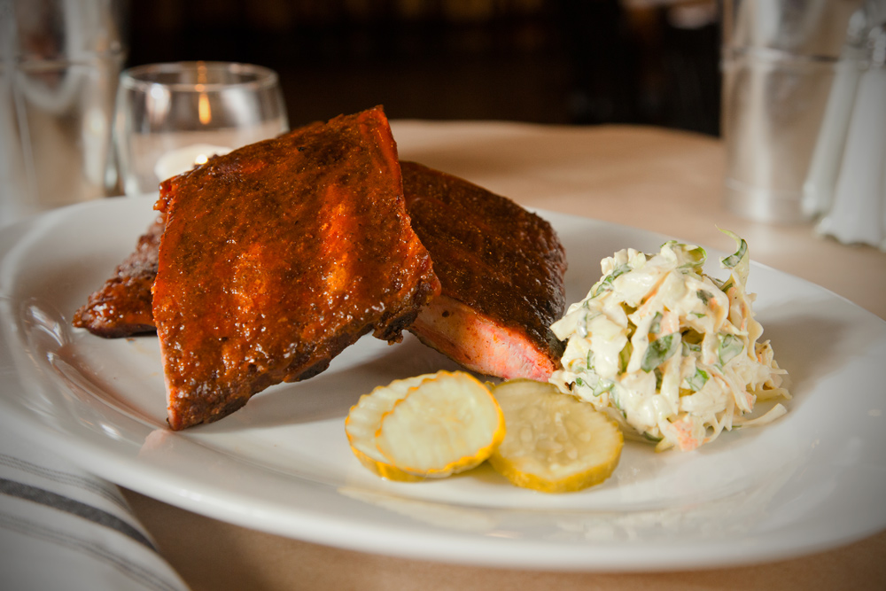 ribs, lemon, and coleslaw on a plate